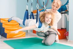 Boy on dual swing. Therapist and happy boy on dual swing stock photo