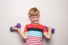 Boy with dumbbells over white background. Studio portrait. Sport. Action royalty free stock photo