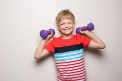 Boy with dumbbells over white background. Studio portrait. Sport. Action stock photography