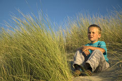 Boy In The Dunes Thinking. A boy sitting between the grass of the dunes looking away and thinking of something. Last hour of the sun before sunset Stock Images