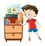 Boy dusting shelf and fishtank Royalty Free Stock Photo