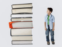 Boy dwarfed by stack of books. Royalty Free Stock Images