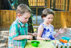 Boy Dyes his Easter Egg Green. A family picture of children painting and decorating eggs.  A boy puts his egg in green dye at a crafts table outside during Royalty Free Stock Photos