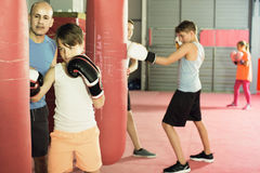 Boy earns accuracy of blows on a boxing bag. Boy with the trainer earns accuracy of blows on a boxing bag in a sports hall Royalty Free Stock Photos