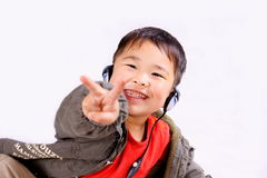Boy with earphone. A picture of a little chinese boy listening to music with earphone, having great fun Royalty Free Stock Image
