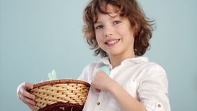 Boy with Easter basket. Teenager shows on his outstretched hand a gently blue Easter egg stock video footage