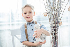 Boy with easter bunny. Cute little boy holding decorative easter bunny and smiling at camera Royalty Free Stock Photos