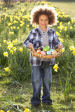 Boy On Easter Egg Hunt In Daffodil Field. Smiling royalty free stock photos
