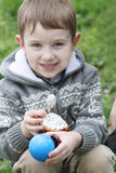 Boy with Easter eggs and cake outdoor Royalty Free Stock Photos