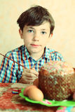 Boy  easter paint eggs and decorate cake Stock Photos
