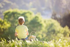 Boy at easter time. Cheerful little boy with basket full of easter eggs after egg hunt in beautiful park at spring time Stock Photo