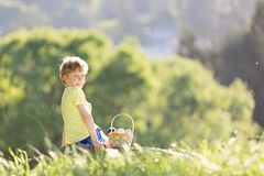 Boy at easter time. Cheerful little boy with basket full of easter eggs after egg hunt in beautiful park at spring time Stock Images