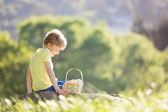 Boy at easter time. Cheerful little boy with basket full of easter eggs after egg hunt in beautiful park at spring time Royalty Free Stock Image