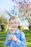 Boy at easter time. Smiling little boy with easter bunny ears holding colorful candy after egg hunt at spring time stock images