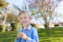 Boy at easter time. Smiling little boy with easter bunny ears holding colorful lollipop at spring time with blooming beautiful tree in the background royalty free stock photo