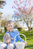 Boy at easter time. Smiling little boy holding easter basket with colorful eggs and bunny at spring time with blooming beautiful tree in the background stock images