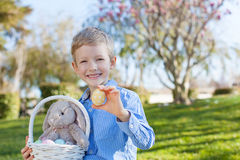 Boy at easter time. Smiling little boy holding easter basket with colorful eggs and bunny at spring time with blooming beautiful tree in the background royalty free stock photography