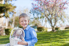 Boy at easter time. Smiling little boy holding easter basket with colorful eggs and bunny at spring time with blooming beautiful tree in the background royalty free stock images