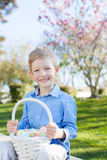 Boy at easter time. Smiling little boy holding easter basket with eggs after egg hunt at spring time stock photos