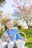 Boy at easter time. Smiling little boy holding easter bunny and basket with eggs after egg hunt at spring time royalty free stock image
