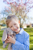 Boy at easter time. Smiling little boy holding easter bunny at spring time with blooming beautiful tree in the background stock photography