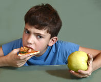 Boy eat pizza slice look at the apple. Preteen boy eat pizza slice look at the apple close up photo Royalty Free Stock Images