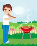 Boy eat sausage fried on the grill Stock Images
