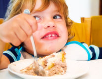 Boy eateing cake. A child laughing while eating a cake Royalty Free Stock Images
