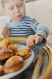 Boy eating. Boy touching a cake in the plate Royalty Free Stock Images
