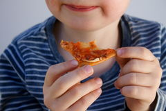 Boy eating. Young blond boy eating pizza stock photo
