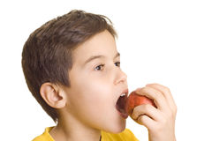 Boy eating apple. Boy biting a red apple royalty free stock photo