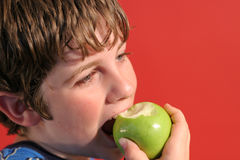 Boy eating an apple stock photo