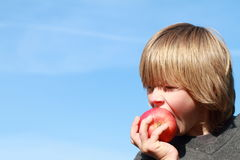 Boy eating an apple. Little boy eating a red apple with sky behind royalty free stock photography