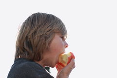 Boy eating an apple. Little boy eating a red apple with sky behind royalty free stock image