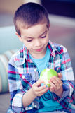 Boy eating apple. Boy in recess eating green apple, looking at it Royalty Free Stock Photos