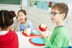 Boy eating apple at school royalty free stock photography