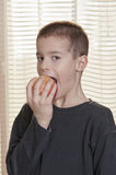 Boy eating apple side view Stock Photo