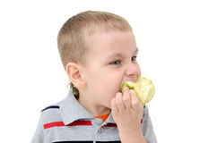 Boy eating an apple on a white background Royalty Free Stock Photography