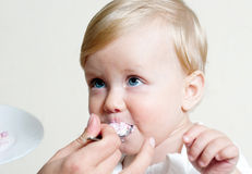 Boy eating baby food with spoon Royalty Free Stock Image