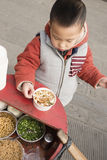 Boy eating Bean Curd Pudding. Chinese boy stand on pavement eating Bean Curd Pudding Stock Photo