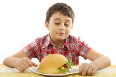 Boy eating a big hamburger Royalty Free Stock Photography