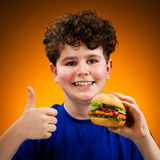 Boy eating big sandwich showing OK sign Royalty Free Stock Images