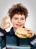 Boy eating big sandwich Stock Photography