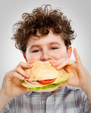 Boy eating big sandwich Stock Photos