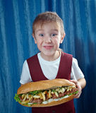 Boy eating big sandwiches Royalty Free Stock Photos