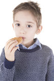 Boy eating a biscuit Royalty Free Stock Images