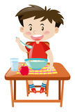 Boy eating from bowl on the table Stock Photos