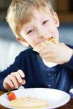 Boy eating breakfast stock photography
