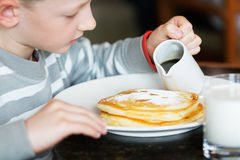Boy eating breakfast Stock Image