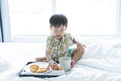 Boy is eating breakfast on the bed in the morning stock photos